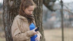 Menina séria grávida dos jovens no revestimento raro do vintage bege e no tshirt dos azuis marinhos que batem seu smartphone no c video estoque