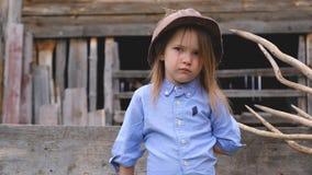 Menina séria na roupa azul e em um capacete empoeirado de construção velho vídeos de arquivo