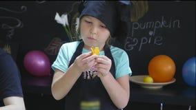 Menina séria no chapéu do cozinheiro chefe e avental que faz petiscos na escola culinária vídeos de arquivo