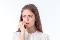 Menina séria nova dedos mordidos e pensamento isolados no fundo branco Imagens de Stock Royalty Free