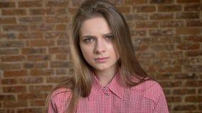 A menina séria nova está dobrando suas testas, decepção, olhando na câmera, fundo do tijolo filme