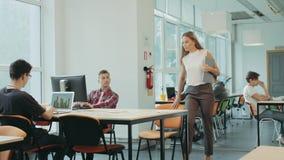 Menina séria que vem no espaço coworking Homens novos que trabalham no espaço aberto video estoque