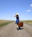 Menina só com a mala de viagem na estrada secundária. imagens de stock royalty free