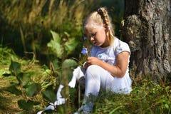 A menina só em um vestido branco e em uma flor em sua mão senta-se perto de uma árvore na tarde imagens de stock royalty free