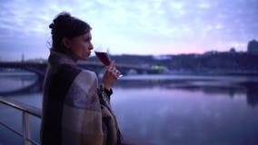 Menina só em uma posição do tapete no balcão do hotel que negligencia o rio e que bebe o vinho tinto de um vidro de vinho filme