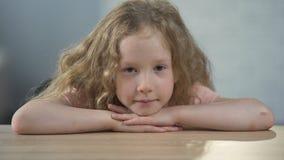 Menina só que senta-se na tabela e que olha na câmera, orfanato filme