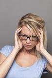 Menina 20s loura na moda na dor que tem a enxaqueca ou o tinnitus Foto de Stock