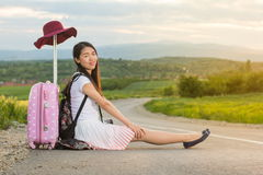 Menina só que senta-se na estrada Fotografia de Stock