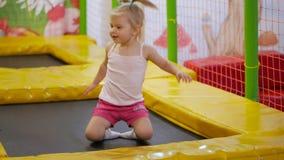 A menina salta em um trampolim interno multi-colorido brilhante filme
