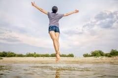 A menina salta na praia, levantando suas mãos para o céu fotografia de stock