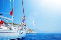 A menina salta no mar de navegar o iate no cruzeiro do verão Aventura do curso, vela com a criança em férias foto de stock royalty free