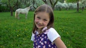 A menina sardenta da cara envia o beijo do ar que olha a câmera Filha no jardim da mola vídeos de arquivo