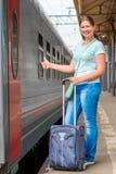 Menina satisfeita com uma mala de viagem que espera um trem Imagem de Stock Royalty Free