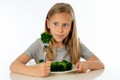 Menina saudável feliz de Yong que come seus vegetais dos brócolis no conceito saudável comer foto de stock