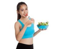 A menina saudável asiática bonita aprecia comer a salada Imagens de Stock