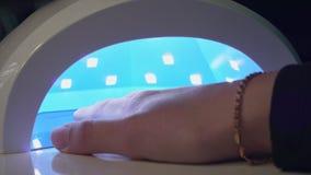 A menina seca o verniz para as unhas no close-up de secagem UV vídeos de arquivo