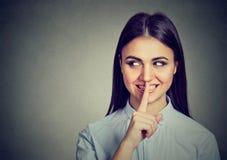 Menina secreta feliz A mulher que diz o silêncio seja quieta com o dedo no gesto dos bordos Imagens de Stock