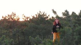 A menina selvagem desportiva ativa do ruivo escala acima na parte superior do pinheiro Floresta conífera do tiro aéreo filme