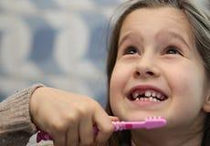 menina sem um dente ao escovar os dentes imagem de stock