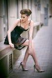 Menina sensual com os pés longos, o vestido preto curto e os saltos altos sentando-se no banco Jovem mulher bonita que veste a sa Imagem de Stock