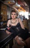 Menina sensual com pés longos e os saltos altos que sentam-se na cadeira em beber da barra Menina bonita com corpo lindo nos salt Foto de Stock Royalty Free