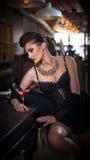 Menina sensual com pés longos e os saltos altos que sentam-se na cadeira em beber da barra Menina bonita com corpo lindo nos salt Fotografia de Stock