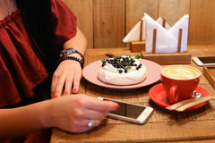 A menina senta e guarda as mãos na tabela ao lado da ordem de merengues, c foto de stock royalty free