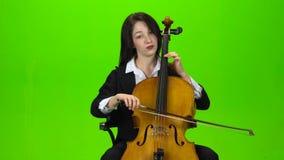A menina senta e joga o violoncelo Tela verde video estoque