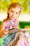 A menina senta o livro de leitura Imagens de Stock