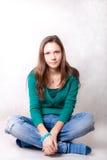 A menina senta-se fotografia de stock
