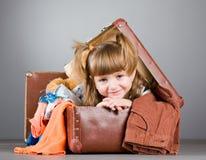 A menina senta-se alegre em uma mala de viagem velha Imagens de Stock Royalty Free
