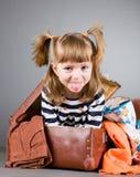 A menina senta-se alegre em uma mala de viagem velha Foto de Stock Royalty Free