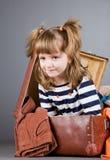 A menina senta-se alegremente em uma mala de viagem velha Imagens de Stock Royalty Free