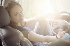 A menina senta-se atrás da roda de um carro Foto de Stock Royalty Free