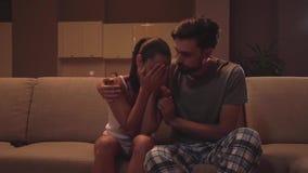 A menina senta-se com o indivíduo no sofá Está gritando A mulher cobre a cara com as mãos e a agitação com a cabeça do heer de um