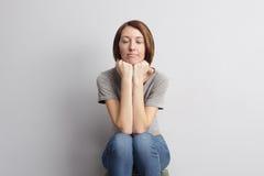 A menina senta-se com suas mãos no queixo, e sonha-se ou pensa-se Fotos de Stock