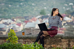 A menina senta-se com um portátil na natureza Foto de Stock