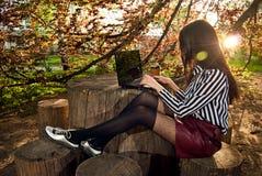 A menina senta-se com um portátil na natureza Fotos de Stock Royalty Free