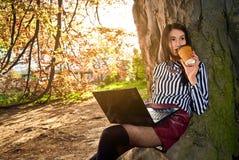 A menina senta-se com um portátil na natureza Fotografia de Stock