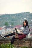 A menina senta-se com um portátil na natureza Imagens de Stock Royalty Free