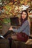 A menina senta-se com um portátil na natureza Fotos de Stock