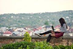 A menina senta-se com um portátil na natureza Imagens de Stock