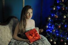 A menina senta-se com uma caixa vermelha fotos de stock