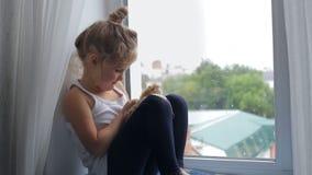 A menina senta-se e joga-se com um brinquedo