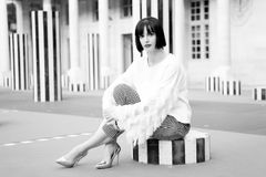 A menina senta-se em coluna listrada em Paris, france Foto de Stock
