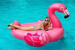 A menina senta-se em flamingos infláveis do colchão Fotografia de Stock