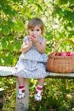 A menina senta-se em um banco foto de stock