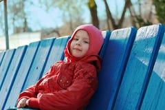 A menina senta-se em um banco no parque Fotos de Stock