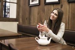 A menina senta-se em um café e guarda-se um copo em suas mãos fotos de stock