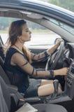 A menina senta-se em um carro como um motorista Imagem de Stock